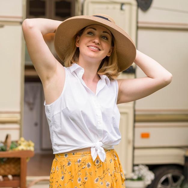 Mulher sorridente com chapéu curtindo uma viagem com uma caravana Foto gratuita