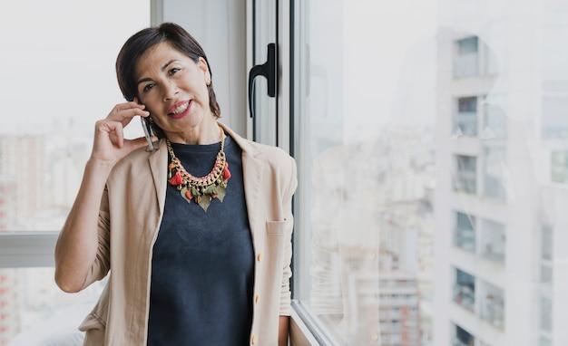 Mulher sorridente com colar falando ao telefone Foto gratuita