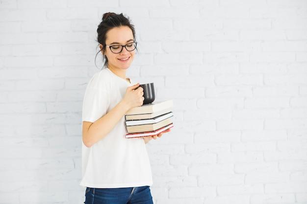 Mulher sorridente, com, copo, e, livros Foto gratuita