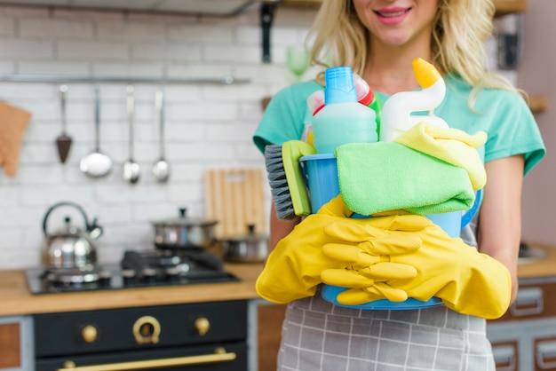 Mulher sorridente com equipamentos de limpeza pronto para limpar a casa Foto gratuita