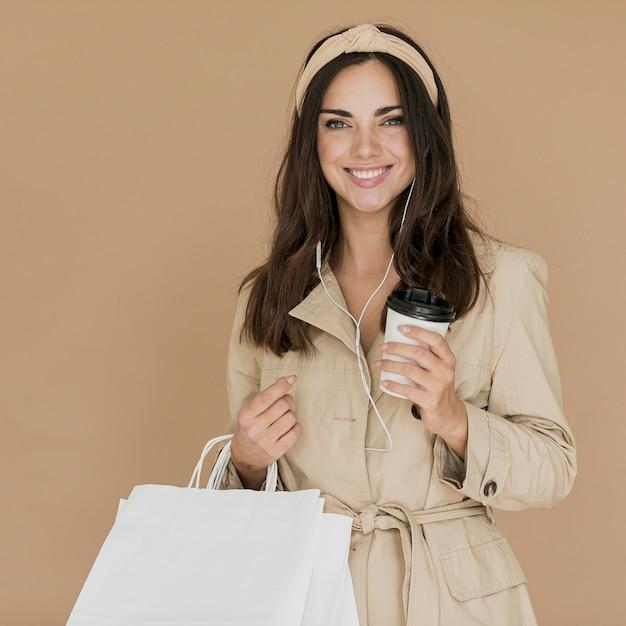 Mulher sorridente com fones de ouvido e sacolas de compras Foto gratuita