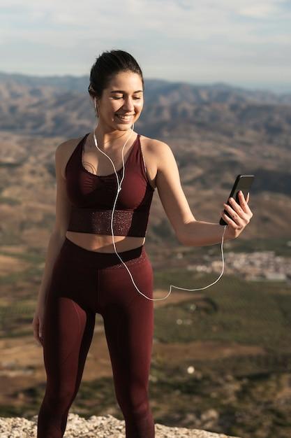 Mulher sorridente com fones de ouvido, olhando para o celular Foto gratuita