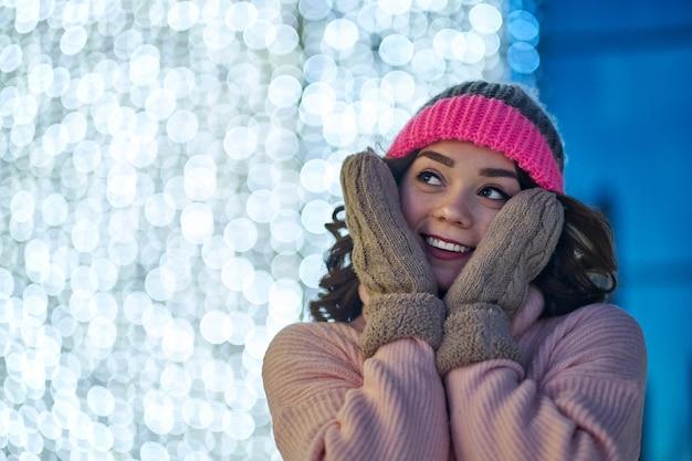 Mulher sorridente com guirlandas e luzes do feriado festivo de natal ou ano novo justo. Foto Premium