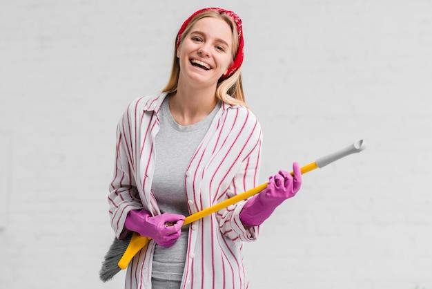Mulher sorridente com luvas cantando na escova Foto gratuita
