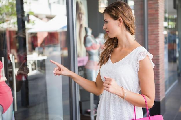 Mulher sorridente com saco de compras apontando a janela Foto Premium