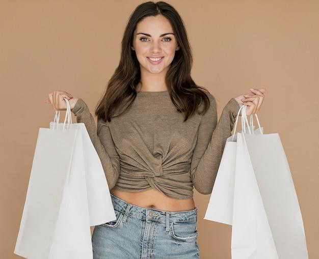 Mulher sorridente com sacolas de compras em ambas as mãos Foto gratuita