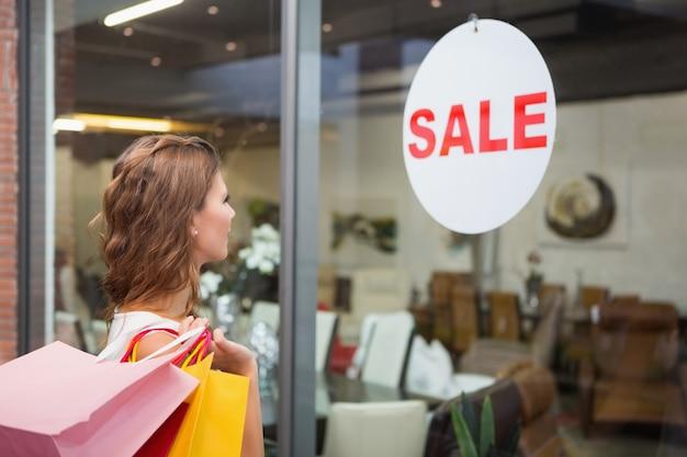 Mulher sorridente com sacolas de compras olhando a janela Foto Premium