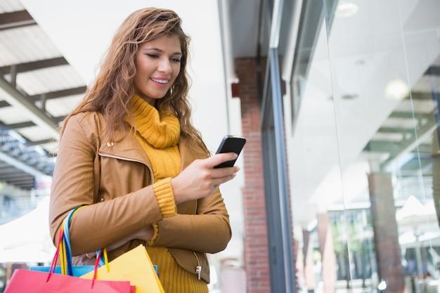 Mulher sorridente com sacolas de compras usando smartphone Foto Premium