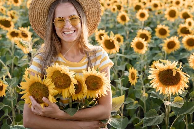 Mulher sorridente com tiro médio segurando flores Foto gratuita