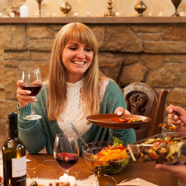 Mulher sorridente com tiro médio segurando o prato Foto gratuita