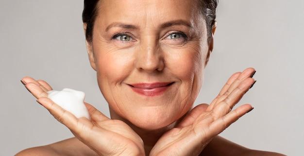 Mulher sorridente com um limpador espumante na mão Foto gratuita
