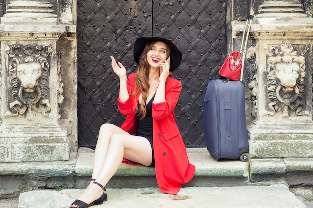 Mulher sorridente com uma mala está falando pelo smartphone nas escadas perto da porta antiga. Foto Premium