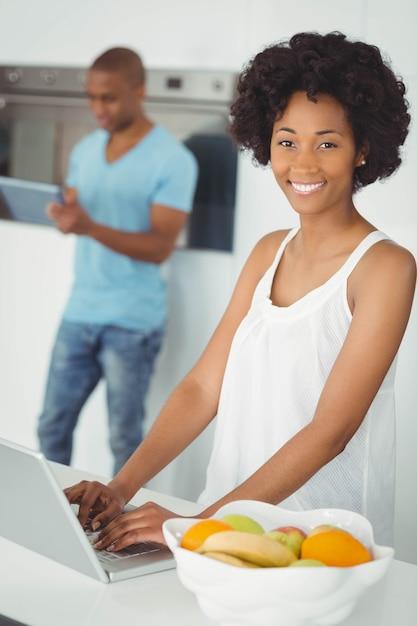 Mulher sorridente, cozinha, usando, laptop, ligado, contador Foto Premium