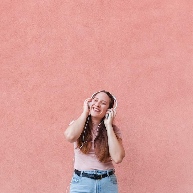 Mulher sorridente curtindo música em fones de ouvido Foto gratuita