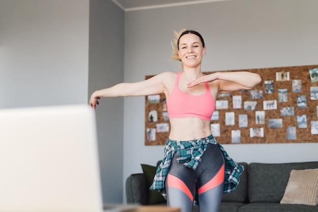 Mulher sorridente dançando no meio da sala de estar se divertindo e vida Foto gratuita