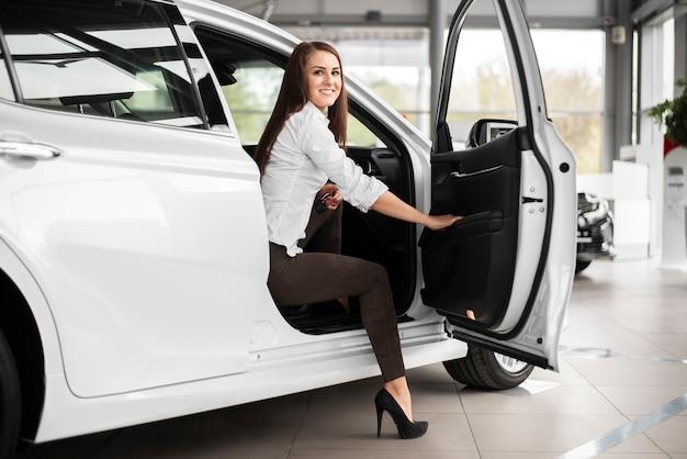 Mulher sorridente de baixo ângulo saindo do carro Foto gratuita
