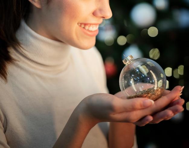 Mulher sorridente de close-up, segurando o globo para árvore de natal Foto gratuita