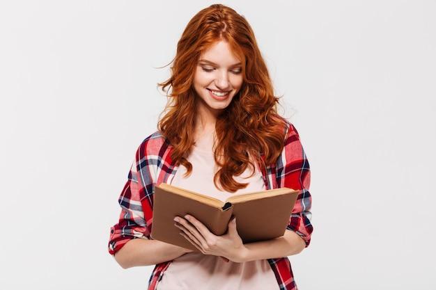 Mulher sorridente de gengibre na camisa segurando e lendo o livro Foto gratuita