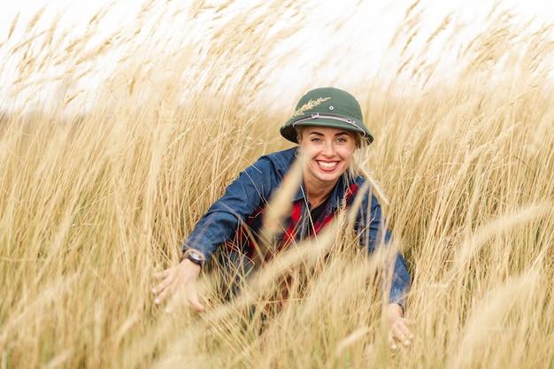 Mulher sorridente, desfrutando de trigo Foto gratuita