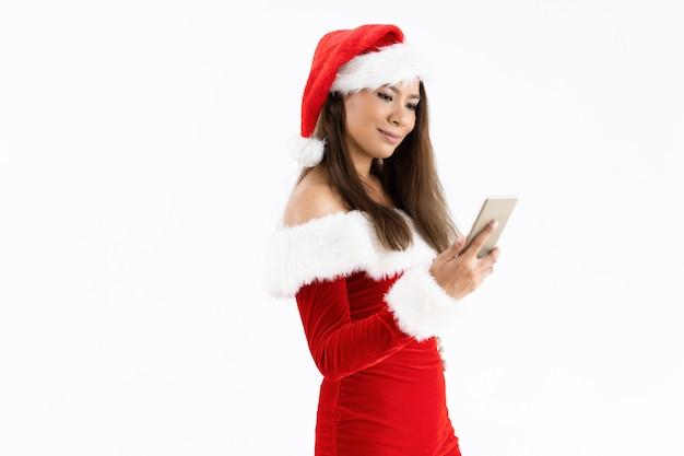 Mulher sorridente, desgastar, traje natal, e, usando, smartphone Foto gratuita