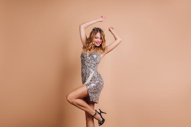 Mulher sorridente despreocupada com roupa glamorosa dançando com as mãos ao alto na festa Foto gratuita