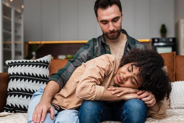 Mulher sorridente dormindo nas pernas do namorado Foto gratuita