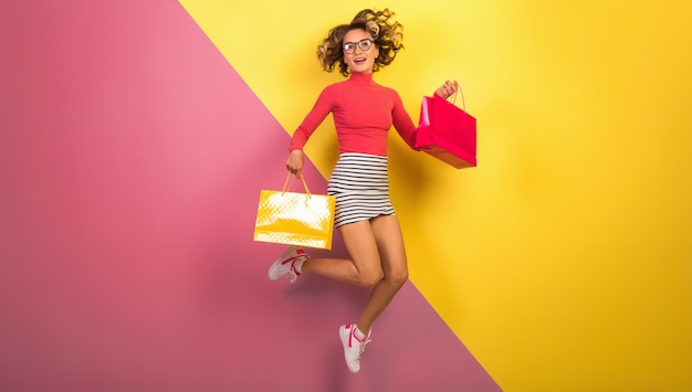 Mulher sorridente e atraente com roupa colorida elegante pulando com sacolas de compras Foto gratuita