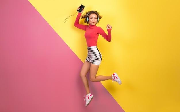 Mulher sorridente e atraente com roupa colorida elegante pulando e ouvindo música em fones de ouvido Foto gratuita