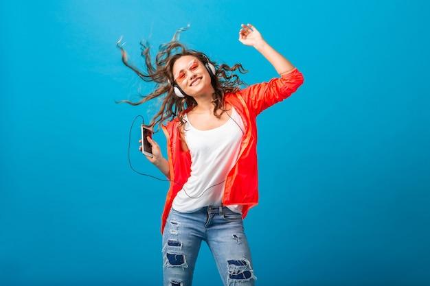 Mulher sorridente e atraente feliz dançando ouvindo música em fones de ouvido, vestida com roupa de estilo hipster isolada no fundo azul do estúdio, vestindo jaqueta rosa e óculos escuros Foto gratuita