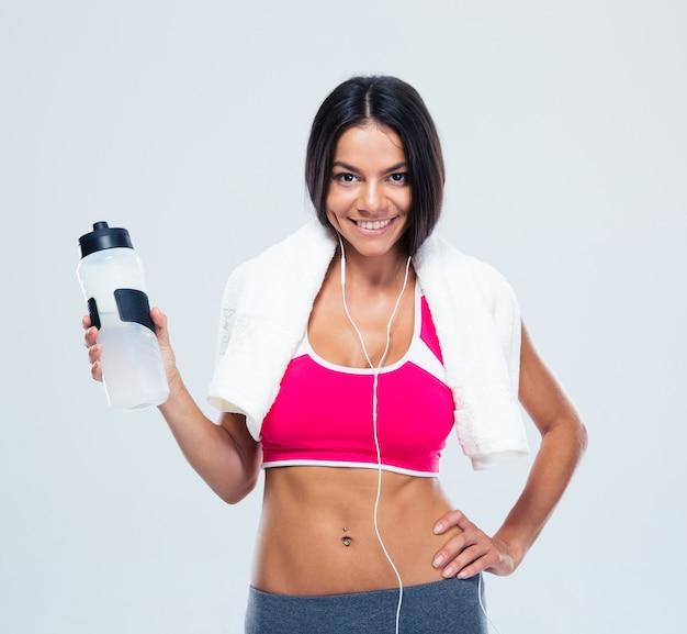 Mulher sorridente e fitness segurando uma garrafa com água Foto Premium