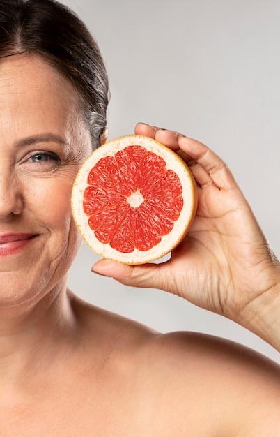 Mulher sorridente e idosa segurando metade de uma toranja Foto gratuita