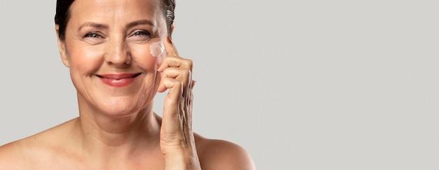 Mulher sorridente e idosa usando hidratante no rosto Foto gratuita