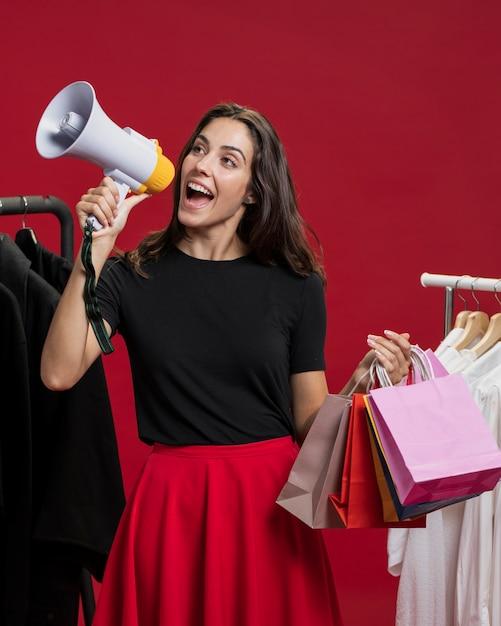 Mulher sorridente em compras gritando com um megafone Foto gratuita