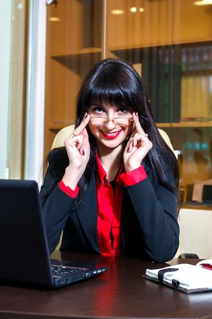 Mulher sorridente em copos se senta em uma mesa no escritório Foto Premium