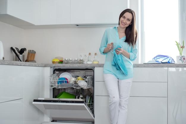 Mulher sorridente em jeans branco e uma camisa turquesa com uma xícara e uma toalha nas mãos, ao lado de uma máquina de lavar louça aberta em um conjunto de cozinha interior branco Foto Premium