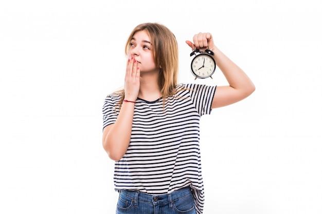 Mulher sorridente em óculos, segurando o relógio despertador Foto gratuita