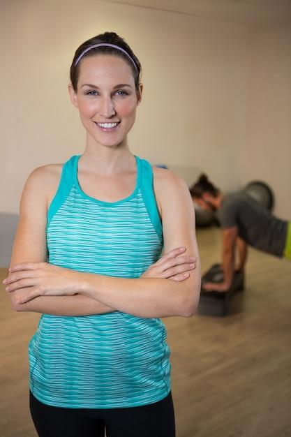 Mulher sorridente em pé com os braços cruzados Foto Premium