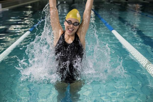 Mulher sorridente, em, swimsuit, pular, em, a, piscina Foto Premium