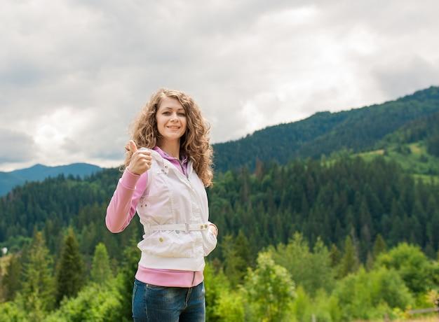 Mulher sorridente em um campo com o polegar para cima Foto Premium