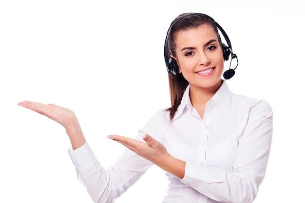 Mulher sorridente em um fone de ouvido apresentando algo Foto gratuita