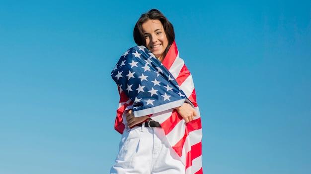 Mulher sorridente, envolvendo grande bandeira dos eua em torno de si Foto Premium