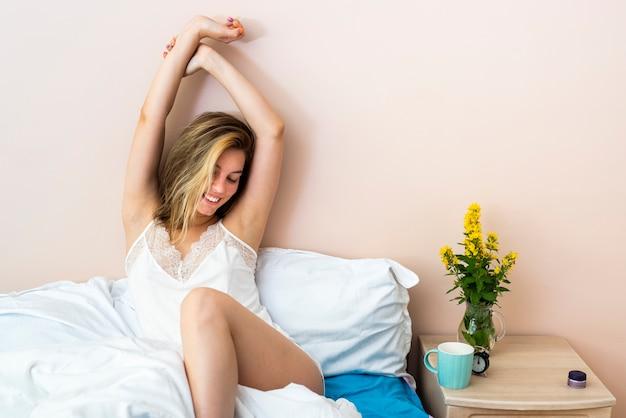 Mulher sorridente, esticar cama Foto gratuita