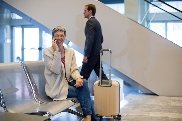 Mulher sorridente falando ao celular na sala de espera Foto gratuita