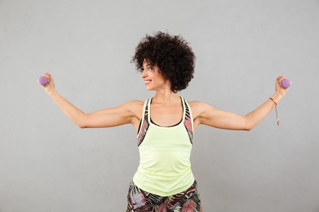 Mulher sorridente fazendo exercício com halteres e mostrando seu bíceps Foto gratuita