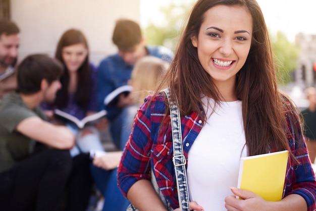 Mulher sorridente fazendo uma pausa na universidade Foto gratuita