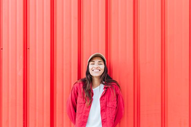Mulher sorridente, ficar, contra, vermelho, ondulado, fundo Foto gratuita