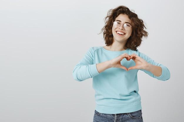 Mulher sorridente fofa e feliz mostrando gesto de coração sobre o peito Foto gratuita