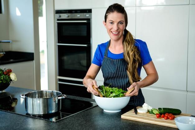 Mulher sorridente jogando uma salada na cozinha Foto Premium