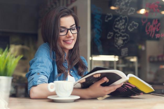 Mulher sorridente lendo jornal em um café Foto gratuita