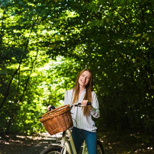 Mulher sorridente, ligado, dela, bicicleta Foto gratuita